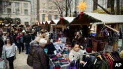 Shoppers look for gifts in booths set up for the holidays around City Hall in Philadelphia, Dec. 8, 2016.