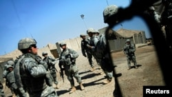 FILE - U.S. soldiers from the 2nd battalion, 32nd Field Artillery brigade listen to their superiors' orders before going on a patrol in Baghdad.
