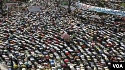 Demonstran melakukan shalat Jumat di lapangan Tahrir di Kairo dalam unjuk rasa 'Revolusi Kedua' (27/5).