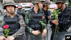 Soldiers hold roses given by supporters at Victory Monument, Bangkok, May 27, 2014.