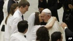 El papa Francisco saluda a una pareja de recién casados en la sala Paulo VI del Vaticano.