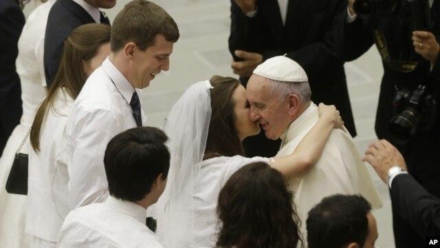 Paus Fransiskus menyalami pasangan pengantin baru dalam acara di Vatikan, Rabu (5/8).