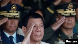 Philippine President Rodrigo Duterte salutes with other military officers during a anniversary celebration of the Armed Forces at a military camp in Quezon city, Manila, Dec. 21, 2016.