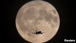 ایک طیارے کے پس منظر میں چوھدویں کا چاند دکھائی دے رہا ہے۔