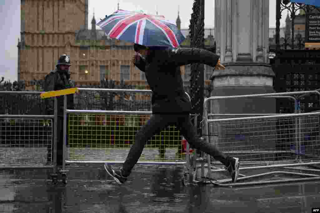 A pedestrian jumps over a puddle on the pavement outside the Houses of Parliament in central London.