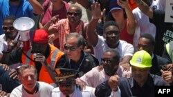Le Père Michael Pfleger (à gauche) et le Révérend Jesse Jackson (à droite) accompagnent Eddie Johnson (C), surintendant de la police de Chicago, lors d'une manifestation contre la violence qui ferme la Dan Ryan Expressway à Chicago le 7 juillet 2018.