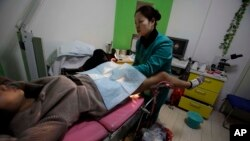 In this 2010 file photo, a nurse examines a patient at an abortion clinic run by Marie Stopes International in Xi'an in central China's Shaanxi province. (AP Photo/Ng Han Guan)
