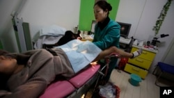 """FILE - A nurse examines """"Nancy"""" Yin, three-months pregnant, at an abortion clinic run by Marie Stopes International in Xi'an in central China's Shaanxi province."""