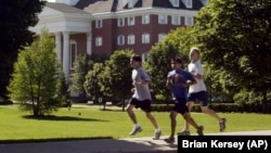 Joggers run through the campus of Wheaton College in Wheaton, Ill.