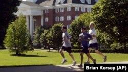Joggers run through the campus of Wheaton College in Wheaton, Ill.