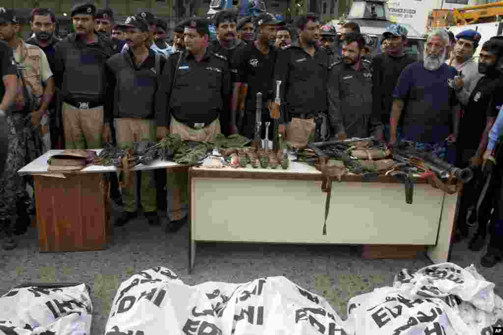 Police officers display confiscated ammunition and the dead bodies of terrorists who attacked the Jinnah International Airport in Karachi, Pakistan, June 9, 2014.
