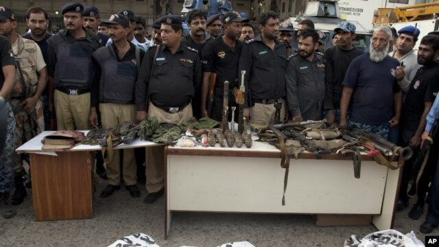 Police officers display confiscated ammunition and the dead bodies of terrorists who attacked the Jinnah International Airport Monday in Karachi, June 9, 2014.
