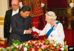 Queen Elizabeth hosts Chinese President Xi Jinping and his wife Madame Peng Liyuan at a state banquet at Buckingham Palace, London, Oct. 20, 2015.