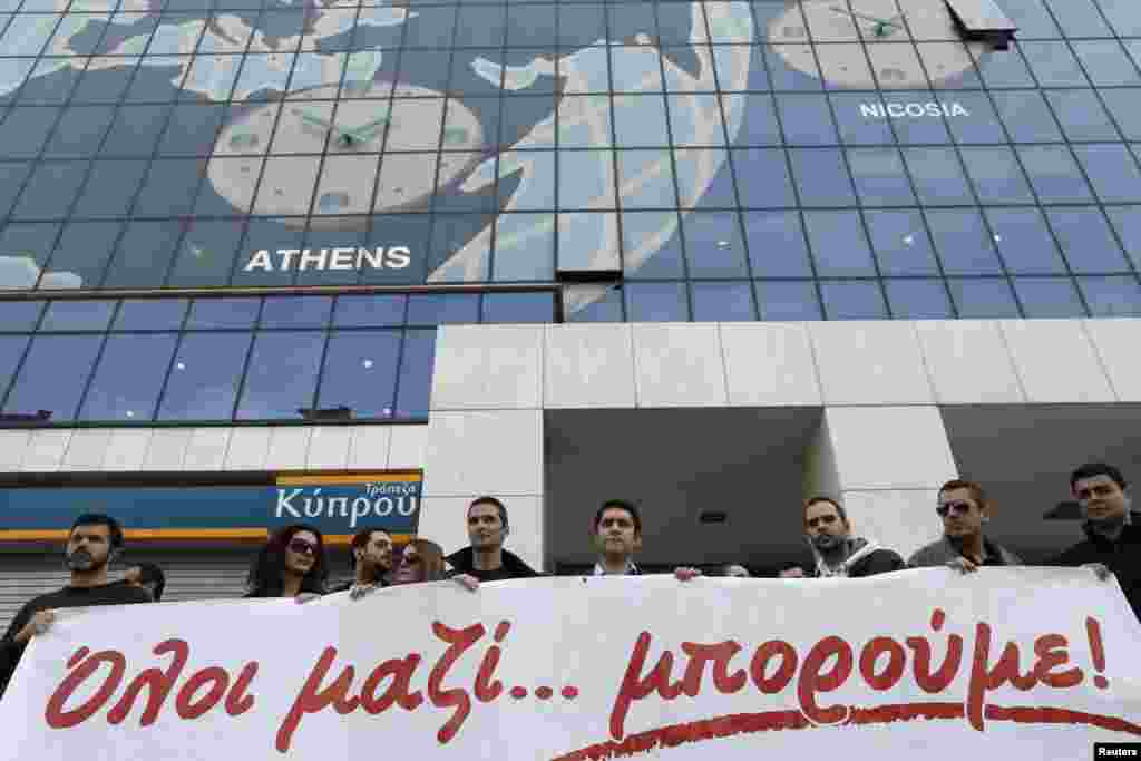 Employees of the Bank of Cyprus take part in a rally in solidarity with Cyprus outside the headquarters of the bank in Athens, Greece, March 20, 2013.