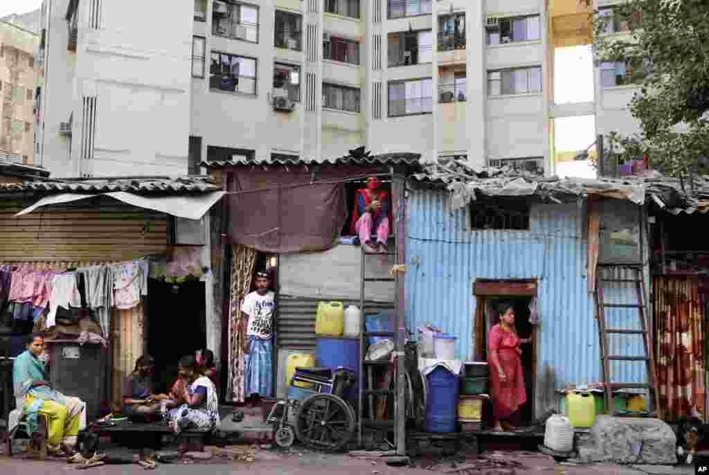 Poor Indians rest by their homes at Dharavi, one of Asia's largest slums, during lockdown measures to prevent the spread of the coronavirus, in Mumbai, India.