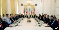 Delegates participate in a bilateral meeting as part of the closed-door nuclear talks with Iran at a hotel in Vienna, Austria, June 12, 2015.