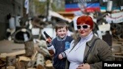 Un niño y su madre posan para una foto frente a una barricada en Slaviansk, al este de Ucrania.