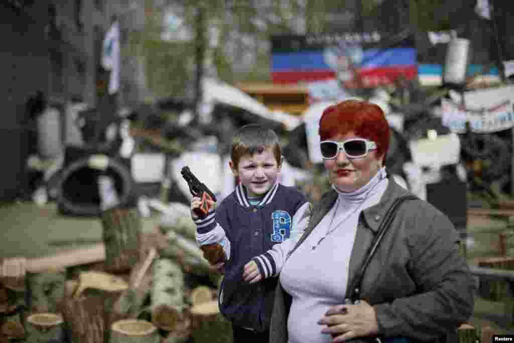 우크라이나 슬라비안스크의 경찰서 앞에서 한 소년이 장남감 총을 들고 포즈를 취하고 있다.