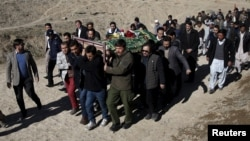 FILE - Mourners carry the body of a bombing victim in Kabul, Afghanistan, Jan. 21, 2016. A day earlier, a Taliban suicide bomber had targeted a minibus carrying Moby Group journalists.