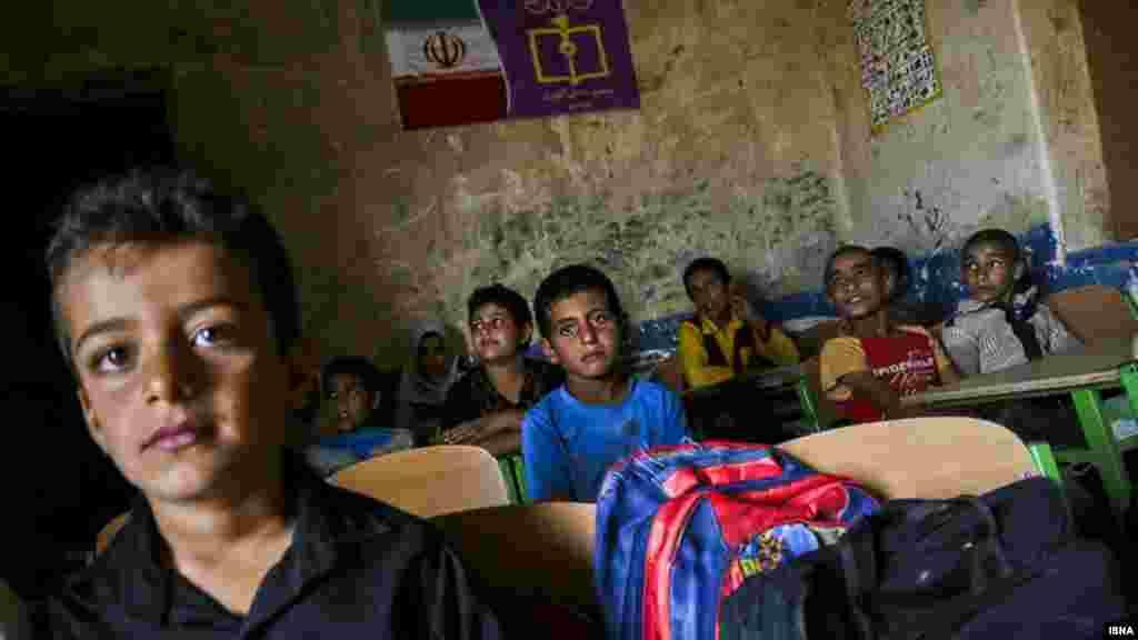 """خبرگزاری ایسنا در گزارش تصویری بنام """"مشق در تاریکی"""" از دانش آموزانی در حاشیه شهر اهواز عکس هایی منتشر کرده که در مناطق محروم در کنار چاههای نفت درس می خوانند. عکس: میلاد اسماعیلی، ایسنا"""