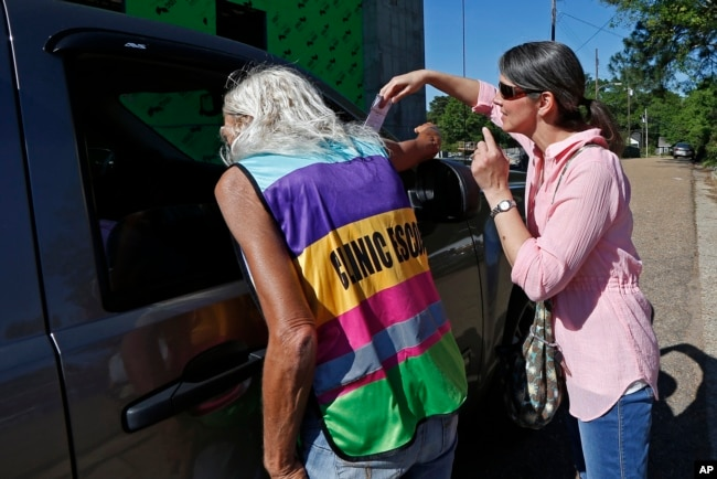 A clinic escort, left, speaks to a driver and patient while an abortion protester attempts to hand over some reading material outside the Jackson Women's Health Organization clinic in Jackson, Miss., April 10, 2019.