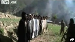 A still image taken from video released by Pakistani Taliban on July 18, 2011 shows masked militants lining up thirteen Pakistani security personnel before shooting them in firing squad style at an unknown location near the border between Pakistan and Afg