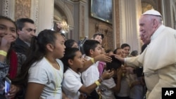 FILE - Pope Francis blesses faithful during his visit to the Morelia Cathedral in Mexico's Michoacan state, Feb. 16, 2016. The clash between the pope and Donald Trump comes just 2 days ahead of the South Carolina Republican primary,