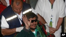 Rescued miner Juan Aguilar waves to the press as he arrives to the hospital in Copiapo, Chile, 14 Oct 2010