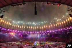 Samba dancers perform as fireworks go off during the closing ceremony in the Maracana stadium at the 2016 Summer Olympics in Rio de Janeiro, Brazil, Sunday, Aug. 21, 2016.