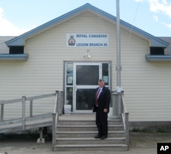 FILE - Gander, Newfoundland, Canada Mayor Claude Elliott stands in front of the Royal Canadian Legion Hall. At this remote town with a population of about 10,000 and an international airport built before World War II, 38 planes carried in 6,600 passengers landed after the September 11 attacks.