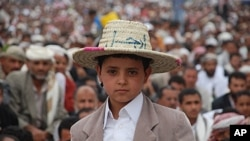"""A young boy wears a straw hat with the Arabic word, """"Leave,"""" during an anti-government demonstration after Friday prayers in the Yemeni capital Sana'a, July 29, 2011"""