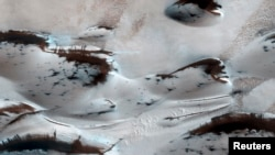 FILE - Water? Not anymore. Mars' northernmost sand dunes are seen as they begin to emerge from their winter cover of seasonal carbon dioxide (dry) ice in this image acquired by the HiRISE camera aboard NASA's Mars Reconnaissance Orbiter, Jan. 16, 2014.