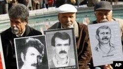 抗议者4月4日在土耳其安卡拉法院前示威,他们手举1980年代一次政变后军人执政时期被处决、被失踪或在监狱中死去的人的画像。
