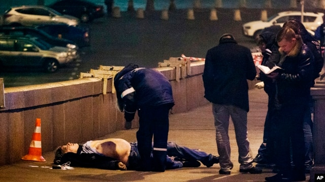 Russian police look at the the body of Boris Nemtsov, a former Russian deputy prime minister and opposition leader near the Kremlin in Moscow, Feb. 28, 2015.