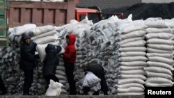 FILE - North Koreans distribute imported sacks of flour on the banks of Yalu River, near the North Korean town of Sinuiju, opposite the Chinese border city of Dandong.