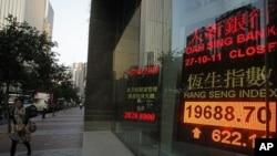 A woman walks past a screen displaying the Hang Seng stock index in Hong Kong, October 27, 2011.
