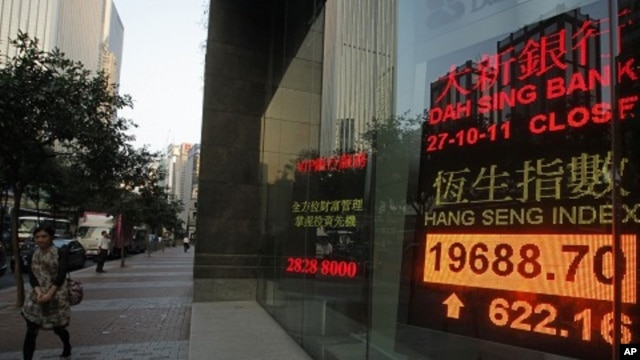 A woman walks past a screen displaying the Hang Seng stock index in Hong Kong, October 27, 2011.