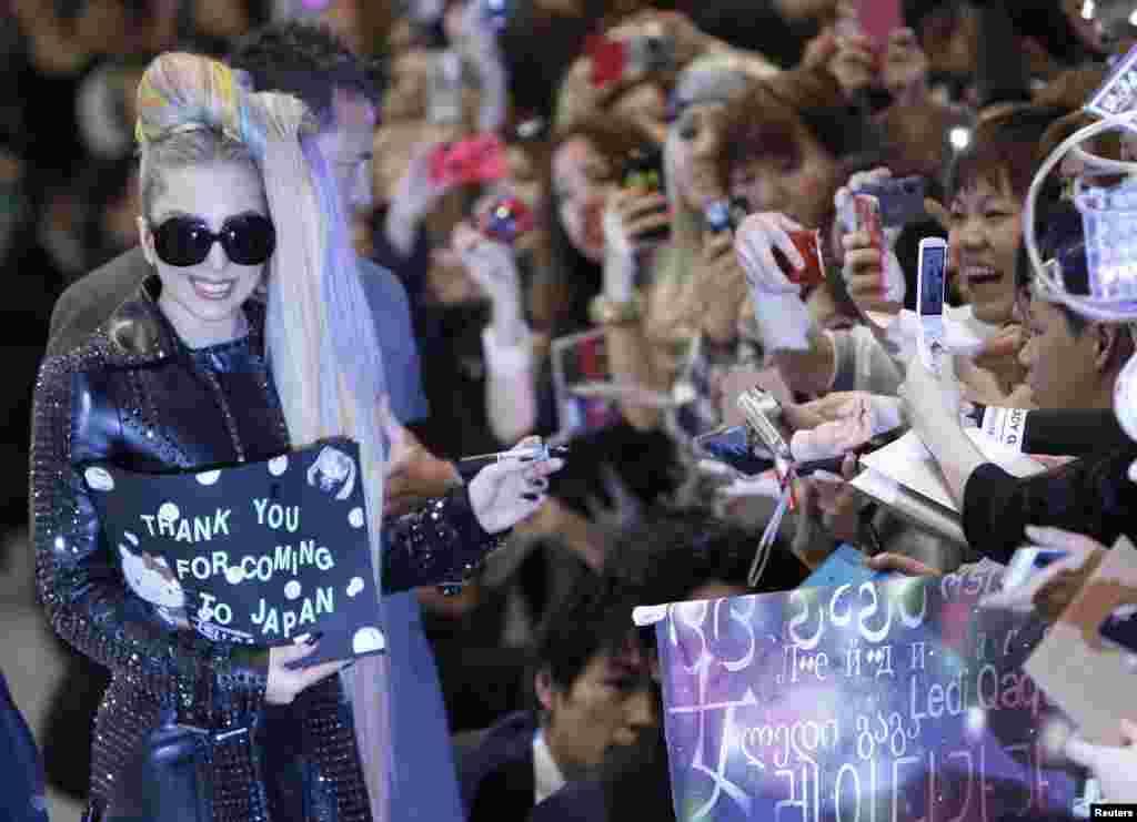 Lady Gaga memberikan tanda tangan kepada para fans sesaat setelah tiba di Bandara Internasional Narita, Tokyo, Jepang, 8 Mei (Reuters).