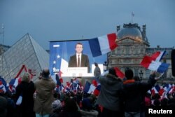 President-elect Emmanuel Macron is seen on a giant screen near the Louvre museum after results were announced in the second round of voting in the 2017 French presidential elections, in Paris, May 7, 2017.