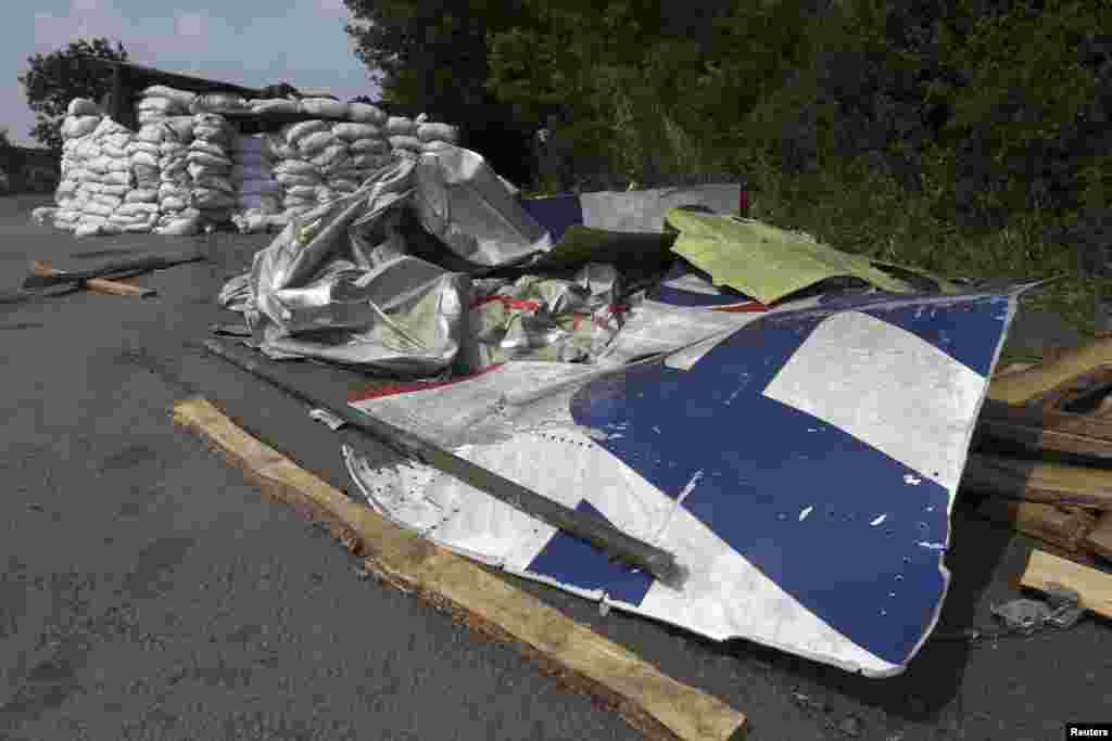 Wreckage lies near a pro-Russian separatist checkpoint at the site of the downed Malaysian airliner MH17 near the village of Rozsypne, in the Donetsk region, Aug. 4, 2014.