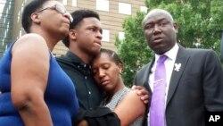Brandt Jean (tengah kiri), saudara dari korban tewas Botham Jean, memeluk adik perempuannya Allisa Charles-Findley, di pengadilan Frank Crowley, Dallas, Senin (10/9).