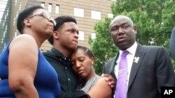 Brandt Jean (au centre) frère de la victime Botham Jean, serre sa sœur Allisa entouré de sa mère, Allison Jean (g), et de l'avocat Benjamin Crump (d) à Dallas le 10 septembre 2018.