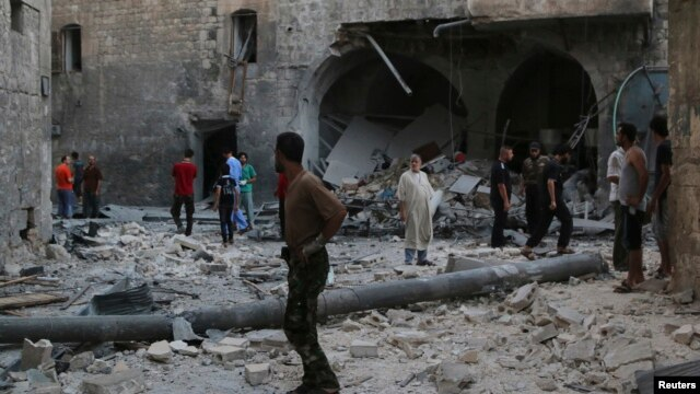 FILE - People inspect a site hit by what activists said was an airstrike by forces loyal to Syria's President Bashar al-Assad, in Qadi Askar district in Aleppo, Syria, July 21, 2014.