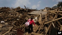 A woman carries her salvaged goods through the rubble of destroyed houses following a massive earthquake in the town of Longtoushan in Ludian County in southwest China's Yunnan Province Wednesday, Aug. 6, 2014. Some 10,000 troops and hundreds of…