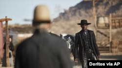 This undated photo provided by Doritos shows Lil Nas X, right, and Sam Elliott in a scene from the company's 2020 Super Bowl NFL football spot.