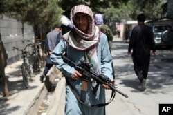 A Taliban fighter stands guard at a checkpoint in the Wazir Akbar Khan neighborhood in the city of Kabul, Afghanistan, Aug. 22, 2021.