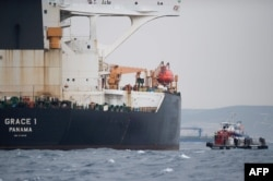 (FILES) In this file photo taken on July 06, 2019 A ship approaches supertanker Grace 1 off the coast of Gibraltar on July 6, 2019. Gibraltar police have arrested the Indian captain and chief officer of a seized Iranian tanker suspected of breaching…
