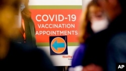 A COVID-19 vaccination appointments sign points the way at Edward Hospital in Naperville, Ill., Dec. 17, 2020.