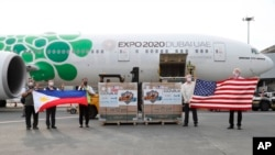 FILE - In this photo released by the National Task Force Against COVID19, US officials hold a U.S. flag as Philippine officials hold the Philippine flag beside boxes containing Johnson & Johnson vaccines as they arrive in Manila, July 16, 2021., J