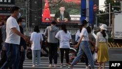 Presiden China Xi Jinping saat berbicara melalui sambungan video dalam sidang Majelis Kesehatan Dunia, tampak di layar raksasa di sebuah jalan di Beijing, 18 Mei 2020.